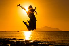 Silhouette of girl jumping against sunrise. Silhouette of happy girl jumping against sunrise at the sea Royalty Free Stock Photos