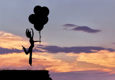 Silhouette of a girl jumping with balloons in the sky Royalty Free Stock Images