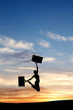 Silhouette of girl jumping with cases Stock Images