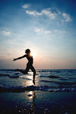 Silhouette of a girl jumping in the ocean Royalty Free Stock Photography