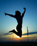 Silhouette of a girl jumping over sunset Stock Images
