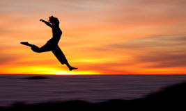 Silhouette of girl jumping in sunset Royalty Free Stock Images