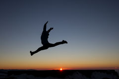 Silhouette of girl jumping in sunset Stock Images