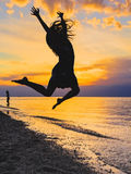 Silhouette of a girl jumping at sunset Stock Photo