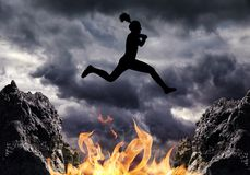Silhouette the girl jumps over fire. Stock Photos