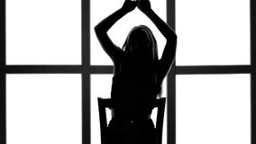 Silhouette of girl with long waving hair in profil on white background with grid window. stock footage
