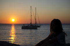 Silhouette of the girl looking at the sea with yachts. In the sunset on a warm summer day Royalty Free Stock Images
