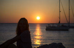 Silhouette of the girl looking at the sea with yachts. In the sunset on a warm summer day Stock Photo