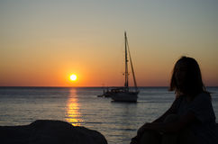 Silhouette of the girl looking at the sea with yachts. In the sunset on a warm summer day Stock Photos