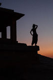 Silhouette of a girl looking at the sunset. Standing on the steps of an ancient temple Royalty Free Stock Photos