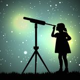 Silhouette of girl looking through a telescope Stock Image