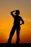 Silhouette of the girl in meditations. A silhouette of the proud young girl found the decision on a sunset Stock Photography