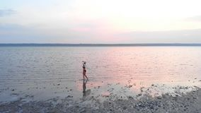 Silhouette of a girl in the middle of lake at sunset. Beautiful girl posing alone in shallow water with light ripples stock video