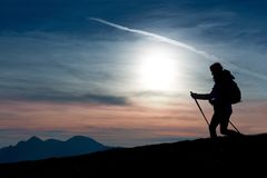 Silhouette of a girl on a mountain during a religious trek in a. Blue and orange sky Royalty Free Stock Image