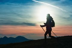 Silhouette of a girl on a mountain during a religious trek in a. Blue and orange sky Royalty Free Stock Images