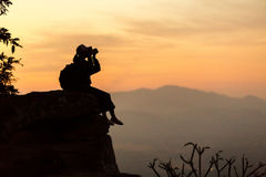 Silhouette girl photographer sitting on the rocks at high shooti Royalty Free Stock Photos