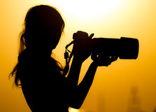 Silhouette of a girl photographer at sunset Stock Image