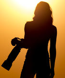 Silhouette of a girl photographer at sunset Stock Photography