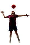 Silhouette of girl playing football Stock Images