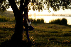 Silhouette of a girl playing a guitar Royalty Free Stock Image