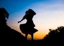 Silhouette girl playing in park at sunset Royalty Free Stock Image