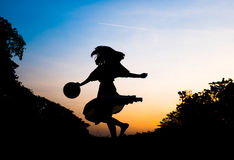 Silhouette girl playing in park at sunset Royalty Free Stock Images