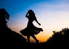 Silhouette girl playing in park at sunset Stock Images