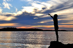Silhouette of girl pointing. The silhouette of a young girl pointing to sky in the archipelago of Stockholm Royalty Free Stock Photo
