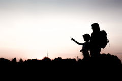 Silhouette of a girl pointing into the distance. Silhouettes of mother and child hiking at sunset. Girl pointing at something distant. Summer vacation in Stock Photos