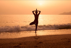 Silhouette of a girl practicing yoga on the sea beach Royalty Free Stock Photos