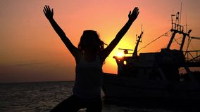 Silhouette of a girl practicing yoga at sunset stock video footage
