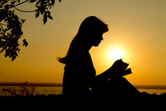 Silhouette of a girl praying. With the Bible Royalty Free Stock Images