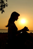 silhouette of a girl praying with the  Bible Stock Photography