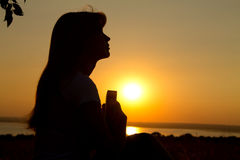 Silhouette of a girl praying with the  Bible Royalty Free Stock Photos