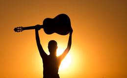 Silhouette of girl with raised guitar Stock Photography