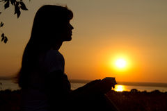 Silhouette of a girl reading at sunset Stock Images