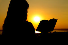 Silhouette of a girl reading at  sunset Stock Photography
