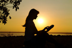 Silhouette of a girl reading at sunset Stock Photo
