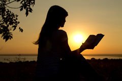 Silhouette of a girl reading at sunset Stock Image