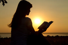 Silhouette of a girl reading at sunset Royalty Free Stock Photography