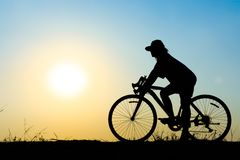 Silhouette girl riding a bike. Silhouette of young woman cyclist on sunset sky with riding along the prairie at yellow evening horizon sea yellow sunset heaven Stock Photos