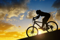 Silhouette of a girl riding a mountain bike Stock Image