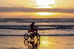 Silhouette of a girl riding tricycle on a beach in a starting tide stock images