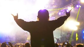 Silhouette of a Girl at a Rock Concert with Hands Outstretched. Music Festival Scene and Lights. Silhouette of a Girl at a Rock Concert with Hands Outstretched stock video footage