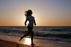 Silhouette girl run on sea coast Stock Photo