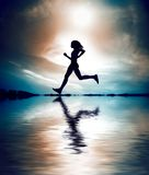 Silhouette of girl running. A silhouette of a girl in mid stride as she runs across a body of water against a blue sky background with clouds Royalty Free Stock Image