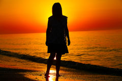Silhouette of a lady running by the sea Stock Images