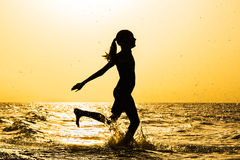 Silhouette of a girl running on the beach at sunset Stock Photos