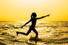 Silhouette of a girl running in the sea Royalty Free Stock Images