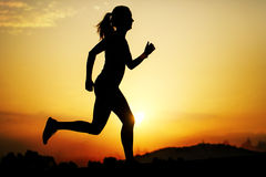Silhouette of girl running at sunset. Royalty Free Stock Photo
